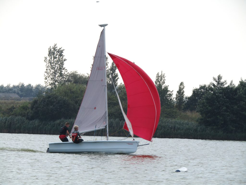 men sailing in dinghy with spinnaker
